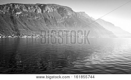 Panoramic view of the winter shores of Lecco Lake Near Bellagio, Lombardy, Northern Italy), taken from the ferry boat. Black and white photo.