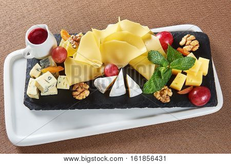 Appetizers served. Top view of a cheese plate with Gouda cheese brie blue cheese walnuts grapes and a little jar of jam