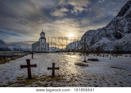 Graveyard and church on Gimsoy with mountain sunset in background Lofoten