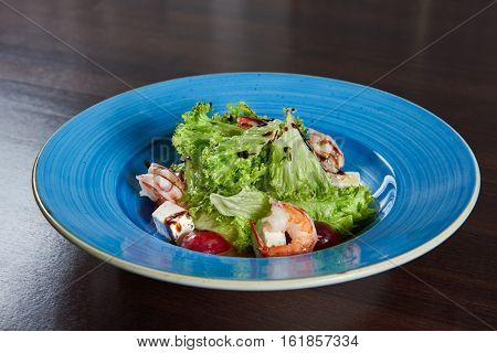 Gotta love the shrimps. Closeup shot of a blue rustic plate full of fresh delicious shrimp salad