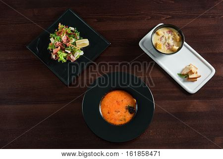 Delicious variety. Top view of variety of restaurant dishes gazpacho tomato cold soup jamon arugula salad and cheese cream soup