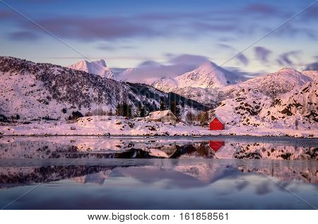 Mountains and cabins at sunset in snowy Steinefjorden Lofoten