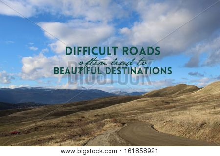 Inspirational quote on scenic mountain landscape view with gravel road along barren fields and hills in autumn with mountains and blue sky with clouds.