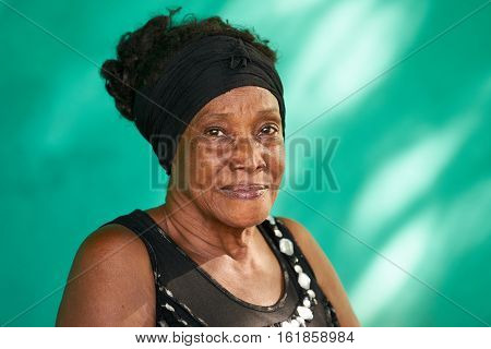 Old Cuban people and emotions portrait of happy senior african american lady looking at camera. Copy space on green wall in background.