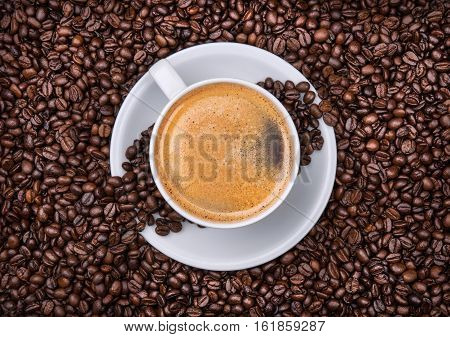 cup of coffee with beans in the background