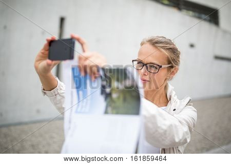 Pretty, female tourist taking a selfie picture while visiting a foreign city and its highlights landmarks, looking happy and relaxed. loving the travel (shallow DOF; color toned image)