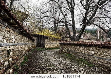 Street with cobble stones of folk museum Zheravna village in Bulgaria. Mountain village