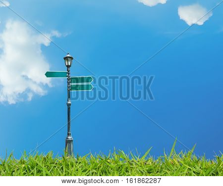 street lamppost and signs with blue sky