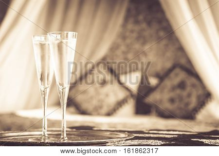 Two Champagne Glasses With Oriental Canopy Bed At The Background