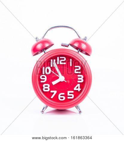 Red vintage alarm clock on white background