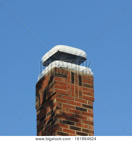Brick Chimney with fresh snow on top and blue sky