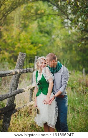 man and woman laughing in the woods on a background of wooden fence