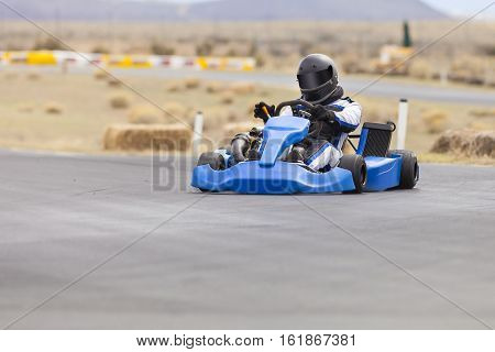 Go Kart Racer in blue car on track