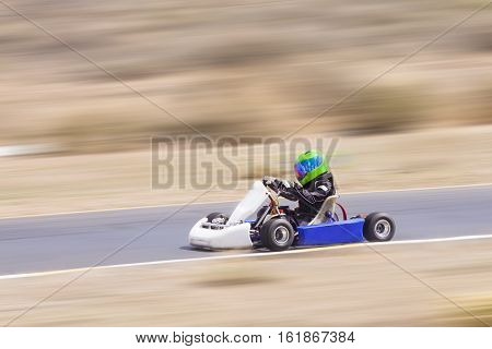Youth Go Kart Racer on Track Panning Shot