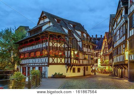 Street with historical half-timbered houses in Petite France district with Maison des Tanneurs (tanners house) Strasbourg France. Evening
