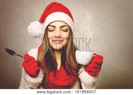 Young woman smiling enjoying coffee wearing red Santa hat, red gloves and scarf, with eyes closed against vintage brownish background. Copy space, retouched.