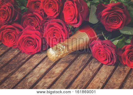 Valentine's day crimson red roses and neck of champagne wine close up, retro toned