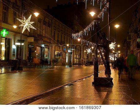 Lamplighter Lodz. Lodz, Poland - December 10, 2016 Art sculpture guardian of street lighting, background Christmas decoration Piotrkowska Street in Lodz