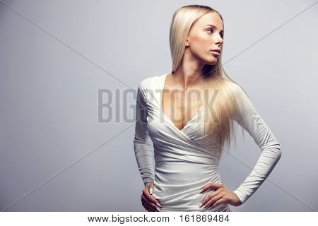 Seductive young woman with hands on hip looking away over gray background