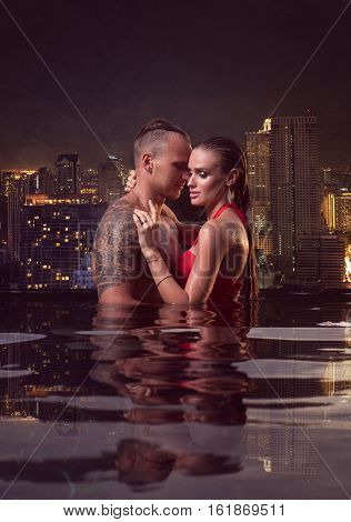 Romantic sensual couple alone in infinity swimming pool over beautiful city view background