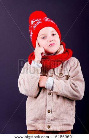 Portrait of a boy wearing red knitted hat scarf and jacket being not satisfied