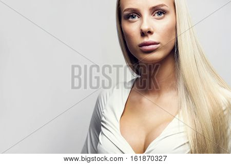 Portrait of young sensuous woman posing over gray background