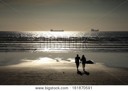 Couple walking on a silhouette sunset beach at Broad Haven, Wales, UK  which is a popular Welsh visitors resort