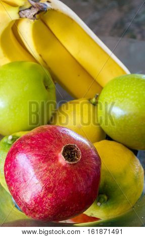 apples, pomegranate and lemons in a bowl