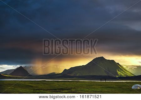 Travel to Iceland. Beautiful Icelandic landscape with mountains, sky and clouds. Trekking in national park Landmannalaugar. Rainy and cloudy Evening in Camping near Alftavatn lake. Tents and hikers in the camping. Travel concept.