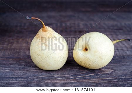 Two yellow pear lying on a wooden surface. Selective focus, low key.
