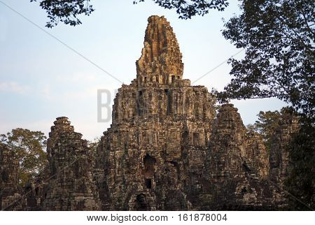A horizontal photographic image of Bayon Temple at sunset in Angkor Thom which is close to Angkor Wat near Siem Reap in Cambodia.