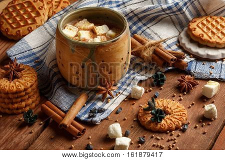 Beautiful ceramic cup with cocoa and marshmallow stands at checkered cloth with cookies anisetree stars cinnamon barks dried barberries on wooden table. Shallow dof. Focus on marshmallow in cup.
