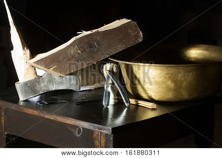 Vintage barber or shaver tools on wooden table. Old razors with blades scissors copper basin broken axe and towel on dark background