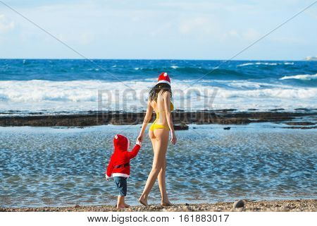 small santa claus cute boy or child barefoot in red new year coat and hat celebrates christmas or xmas holidays at sand beach near sea or ocean water holds hand of pretty woman in yellow swimsuit