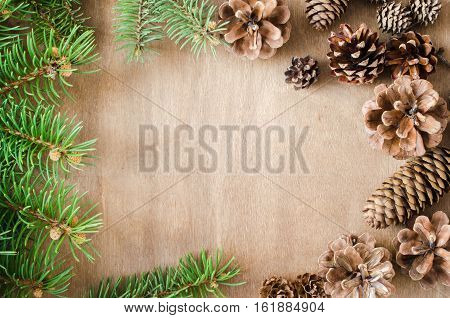Christmas Background. Cones and Branch fir tree in a frame on rustic wooden table with copy space. Top view. Copy space. Selective focus.