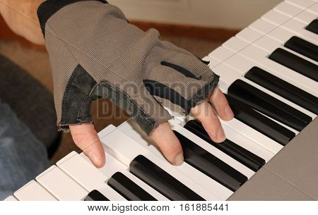 A pianist wears a fingerless glove to keep his hand warm while practicing the piano.