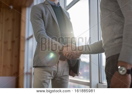 Two Business Man Shake Hand Agreement Coworking Center Business Team Coworkers Stand in front Big Panoramic Window Modern Office