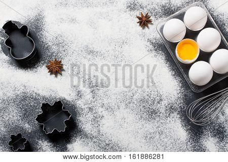 Dark wooden baking background with eggs whisk shape cookie cutter flour and star anise. Horizontal orientation with copyspace top view.