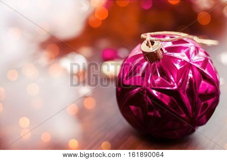 Magenta christmas ball on bokeh background of xmas ornaments. Merry christmas. Winter holidays. Xmas theme. Happy New Year. Blurred background. New Year Background. Copy space.