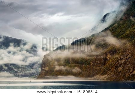 Little boat in cloudy fjord near Flam Norway