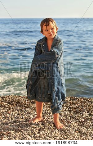 Boy about five years old standing on a pebble beach at the background of the sea on a sunny day. A child dressed in a denim jacket father. Boy swim and wet smiling. Family vacation, fun.