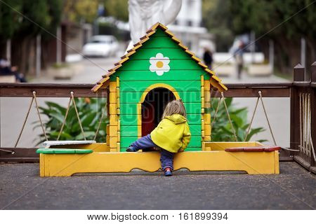 In Park is a small colorful games. House made of wood, brightly painted. In the house painted flower. On the ground plays a little girl in a warm fleece suit. Baby tries to get into the house, throws his leg over the fence. Outdoor warm weather of autumn.