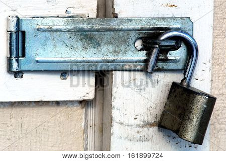 Open grimy lock with hasp closed on a beige door with scarred white trim