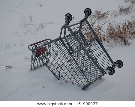 An over turned shopping cart abandoned in the deep snow of a field on a winter day.