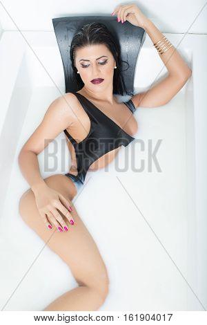 Sexy woman posing in milk bath dressed in black body