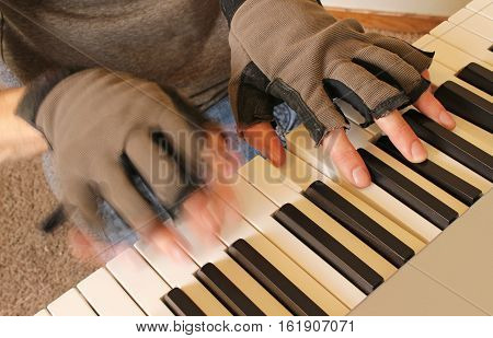A pianist wears fingerless gloves to keep his hands warm while practicing piano. The left hand strikes a chord as the right hand glides over the keys.