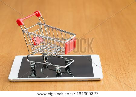 Tablet and shopping cart on wood table Online shopping concept