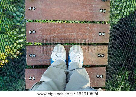 man leg on hanging wood canopy walk way