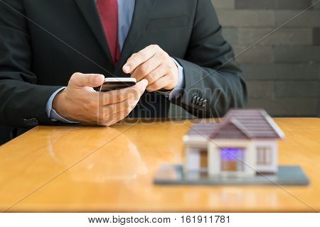 Businessman using mobile application in mobile phone for calculating loan home