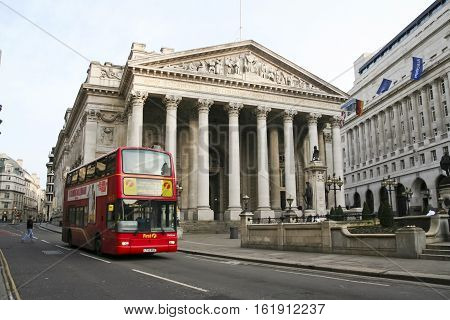 London UK - Jan 17 2009: red 23 bus passing the royal exchange building in the city of london twice destroyed by fire this the third incarnation to stand on the site was opened by queen victoria in 1844 originally used as a centre for commerce it now func